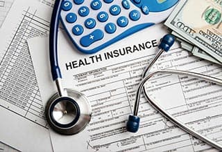 health insurance paperwork with stethescope and calculator