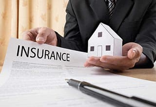 insurance employee holding house and insurance contract